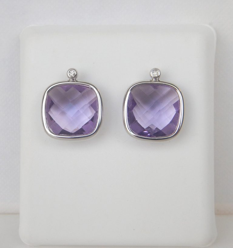 checkerboard cut amethyst earrings resting below a small diamond set in white gold