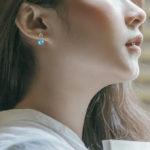 white gold blue topaz and diamond dangle earrings on model