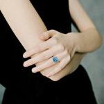 white gold blue topaz and diamond halo ring on model