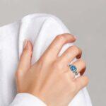 white gold blue topaz and diamond ring on finger