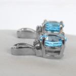 side view of white gold blue topaz and diamond dangle earrings