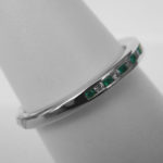 side view of white gold emerald and diamond band