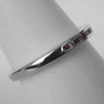 side view of white gold ruby and diamond channel set band