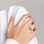 white gold peridot and diamond ring on finger