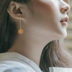 yellow gold flower wire diamond dangle earrings on model