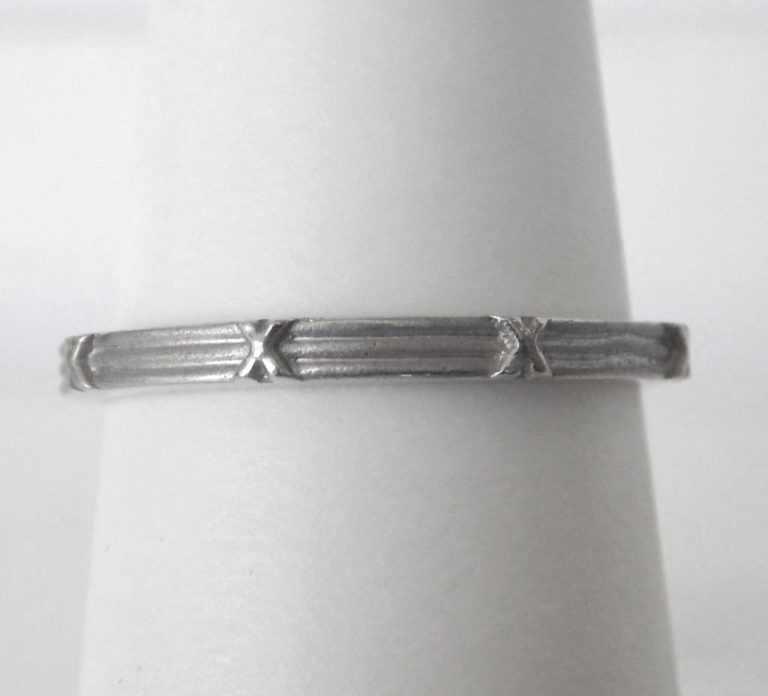 white gold band with small x's on it