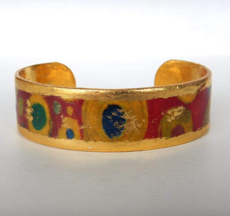 yellow gold cuff bracelet with yellow, blue, and green circular pattern