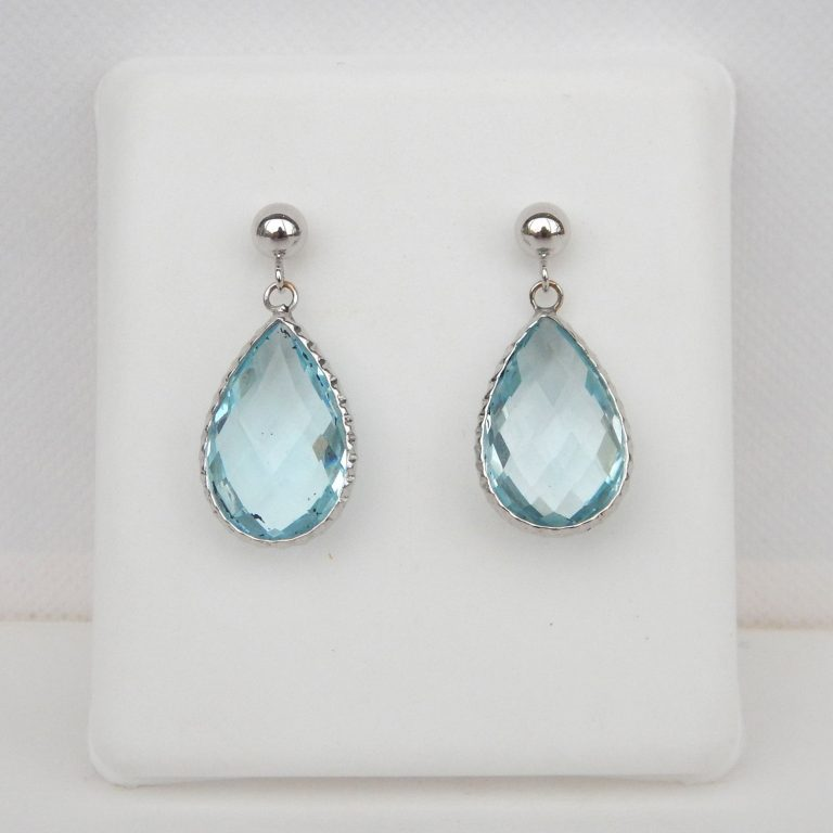tear drop shaped blue topaz dangle earrings in a white gold setting