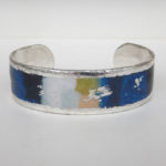 silver cuff bracelet with blue, black, white, and green colors mixed together
