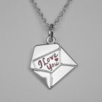 silver pendant in the shape of an envelope with the words