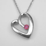 white gold pendant in the shape of a heart with a ruby in the center