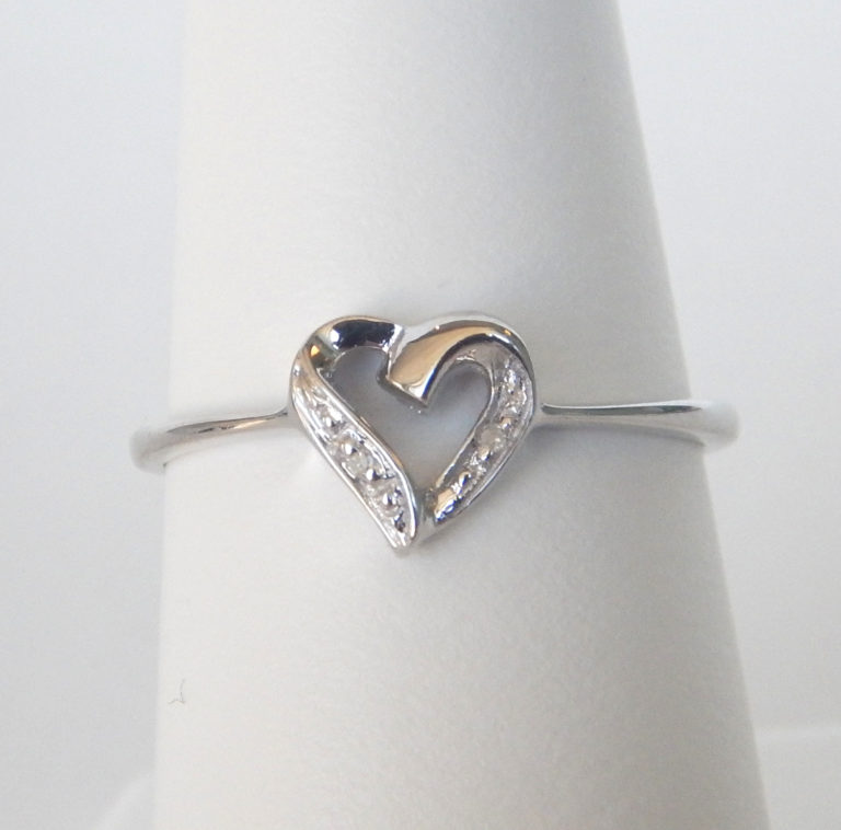 sterling silver ring with diamonds in the shape of a heart in the center