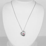 white gold heart necklace with a ruby in the center of the pendant