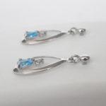 side view of blue topaz and diamond dangle earrings