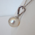 side view of white gold akoya pearl and diamond pendant