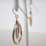 side view of two tone gold dangle earrings