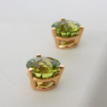side view of round peridot studs in yellow gold basket setting