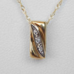 close up view of two tone gold diamond pendant