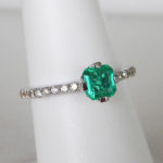 white gold emerald ring with diamonds on the band