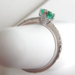 side view of emerald and diamond ring showing the diamond cluster on the ring