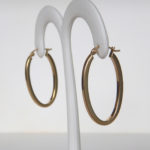 side view of yellow gold oval hoop earrings