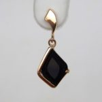 close up view of yellow gold onyx dangle earring