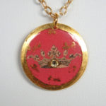 close up view of yellow gold leaf pink disc with gold crown design
