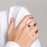 yellow gold garnet and diamond ring on finger