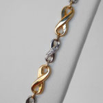 close up view of two tone gold infinity necklace