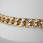 close up view of two tone gold diamond cut cable link bracelet