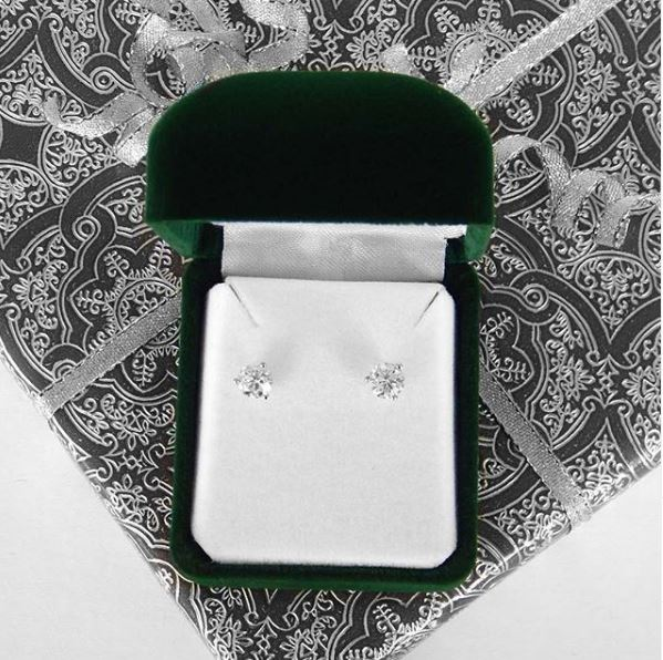 diamond stud earrings on top of a wrapped gift