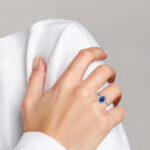 white gold oval sapphire and diamond halo ring on finger