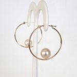 side view of yellow gold pearl hoop earrings