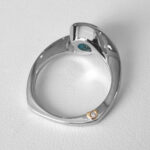side view of white gold blue topaz and diamond ring