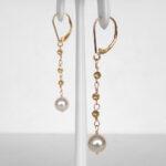 side view of yellow gold akoya pearl dangle earrings